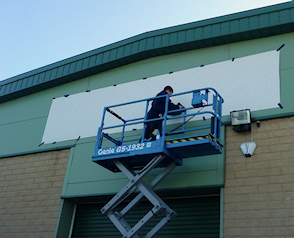 Flat cut acrylic lettering being fixed directly onto a metal cladded industrial unit.